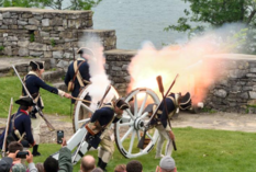Men in colonial army uniforms lighting a cannon at Fort Ticonderoga