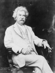 Mark Twain sitting with a cigar in one hand resting on the armrest