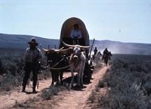 Oregon Trail covered wagons and horsemen