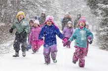 Young children running through snowstorm