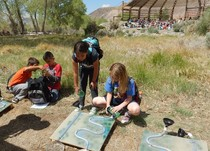 Native American students outdoors working on a science project