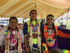 Three high-school age Native American female students in Native regalia