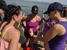 Teachers on boat studying an object with the instructor