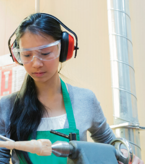 High school girl wearing clear goggles and noise-canceling earphones working an apprenticeship job