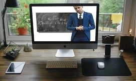 Computer workstation with image of instructor in front of chalkboard on screen