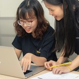 Two elementary school girls working happily on a computer