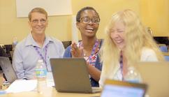 Three teachers enjoying a laugh during a computer science workshop