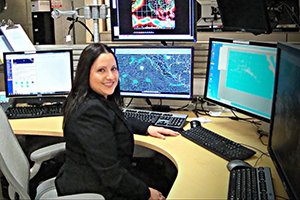 Female weather forecaster sitting before an array of computer screens in a weather service office
