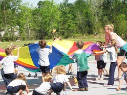 Female teacher and young students with a parachute