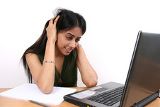 Female students looking perplexed while working on laptop