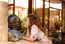 Young girl nose to nose with a bust of Frank Lloyd Wright