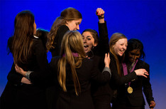 Girls in uniform celebrating winning e National Mock Trial competition