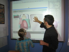 Young female student and male teacher at a Smart Board discussing a lesson on the heart