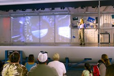 Woman offering a presentation to teachers next to a screen showing a image of the curvature of the Earth