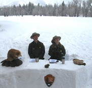 Park rangers sitting outdoors at a desk-shaped mound of snow
