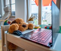 Stuffed dog working the mouse for a laptop