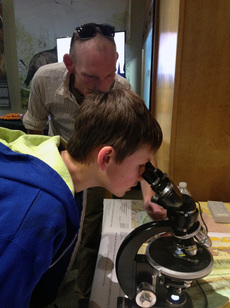 Jack Drew, 11, examined a thin section of granite under the microscope with assistance from WSGS geologist, Jacob Carnes.