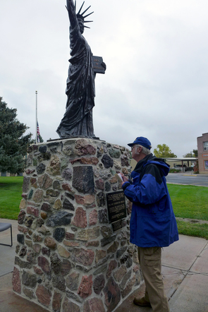 WSGS geologist Wayne Sutherland IDs rocks that comprise the pedestal of the Little Sisters of Liberty statue in Torrington, Wyoming.